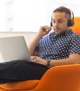 Mann überprüft eine automatische Transkription am Laptop